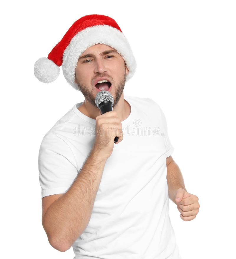 Young man in Santa hat singing into microphone stock photos