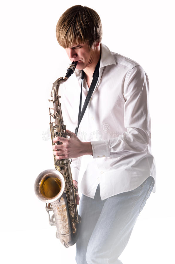Young man with saxophone. Young man playing the saxophone over white background royalty free stock photography