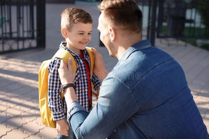 Young man saying goodbye to his little child royalty free stock image
