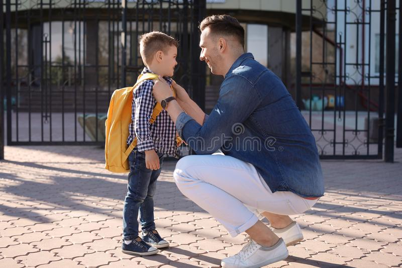 Young man saying goodbye to his little child royalty free stock photo