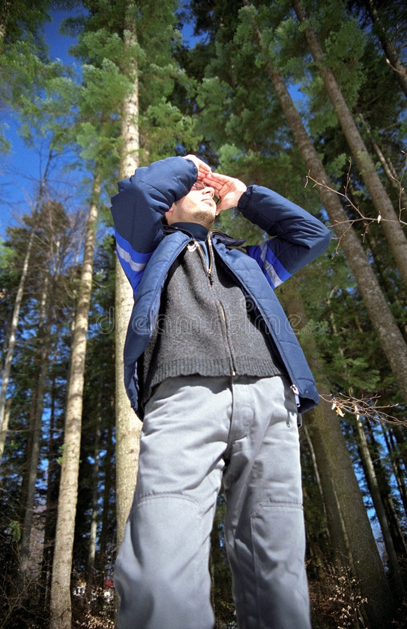 Young man scanning the forest. Young hiker in the forest scanning for his next direction, using his palms to keep his eyes in the shade from the sun. 35mm film stock photo