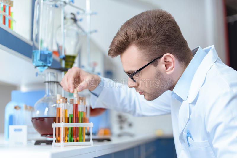 Young man scientist holding test tube with reagent in lab. Side view of young man scientist holding test tube with reagent in lab royalty free stock image
