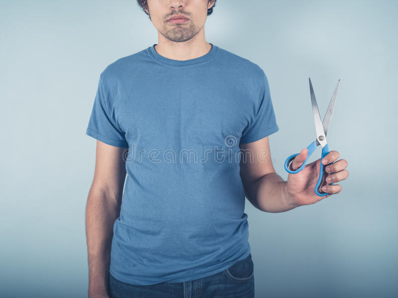 Young man with scissors stock image
