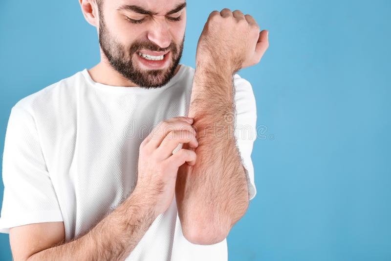 Young man scratching hand on color background. Allergies symptoms. Young man scratching hand on color background, space for text. Allergies symptoms stock photos