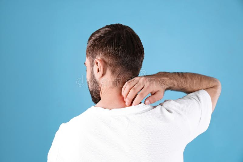 Young man scratching neck. Allergies symptoms. Young man scratching neck on color background. Allergies symptoms stock images