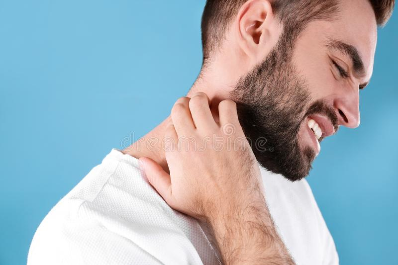 Young man scratching neck. Allergies symptoms. Young man scratching neck on color background. Allergies symptoms royalty free stock photo
