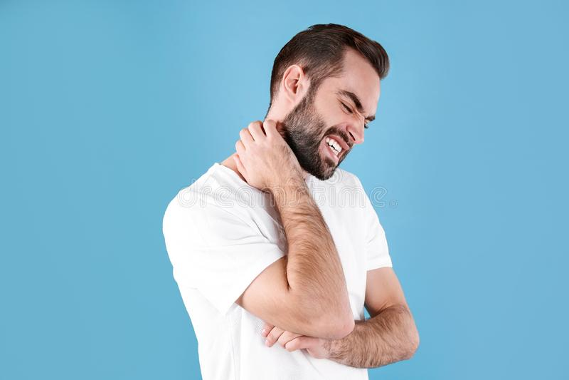 Young man scratching neck. Allergies symptoms. Young man scratching neck on color background. Allergies symptoms stock photos