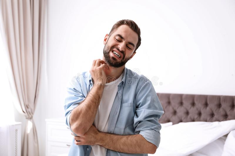 Young man scratching neck. Allergies symptoms. Young man scratching neck indoors. Allergies symptoms stock images