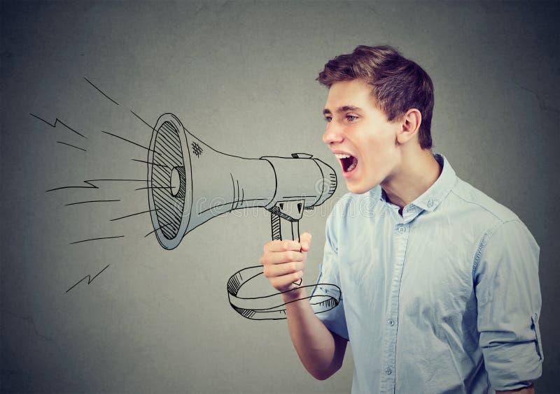 Man screaming in a megaphone making announcement. Young man screaming in a megaphone making announcement stock photo