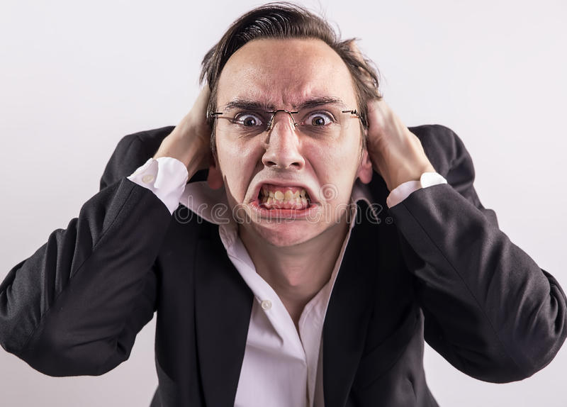 Young man screaming with rage and frustration. Young businessman screaming with rage and frustration stock photo