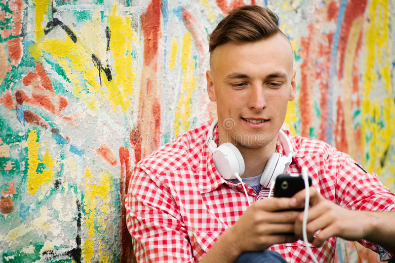 Young man searching through his downloaded music. Young man standing against a grungy exterior wall with graffiti searching through his downloaded music on his stock photo
