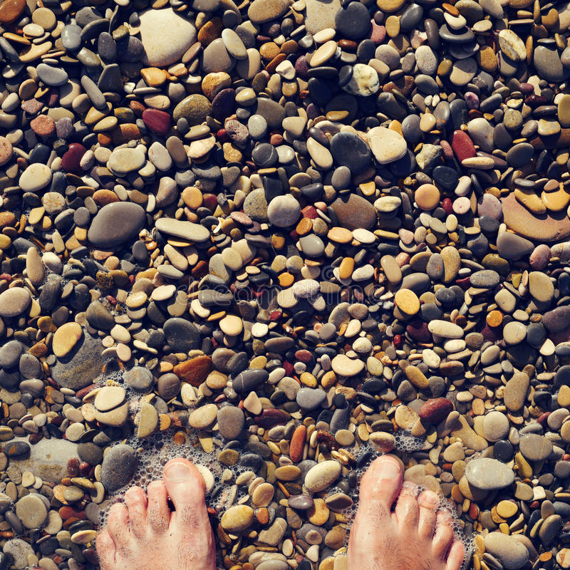 Young man in the seashore of a shingle beach. Closeup of the feet of a young caucasian man in the seashore of a shingle beach royalty free stock photo
