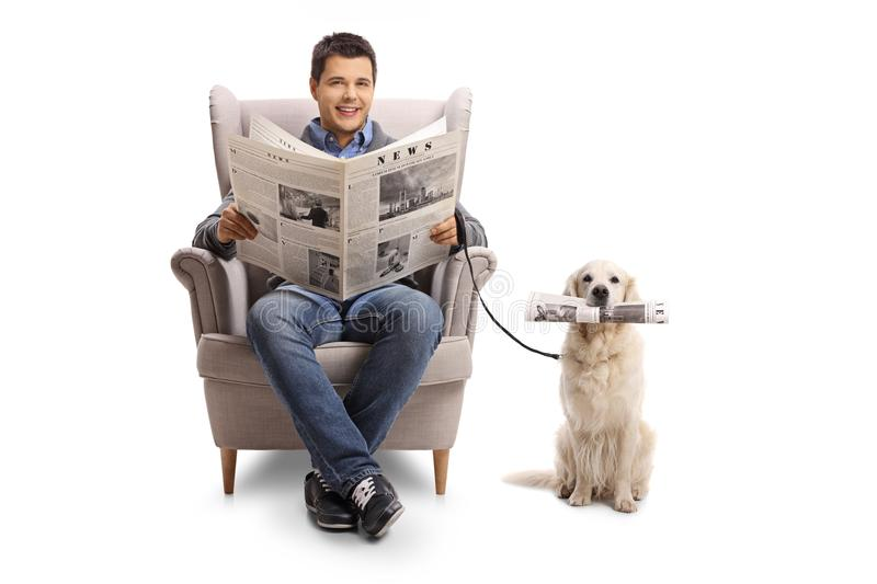 Young man seated in an armchair holding a newspaper and a labrador retriever with a newspaper royalty free stock images