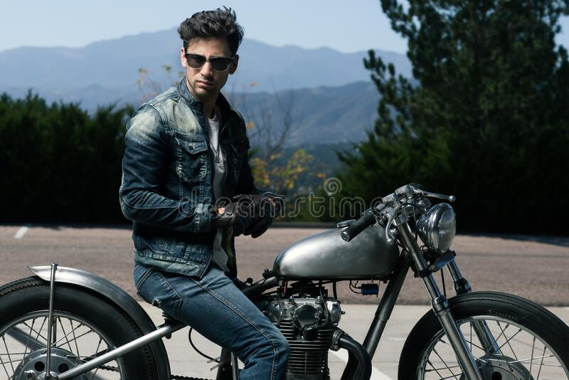 Young man seated on motorbike royalty free stock image