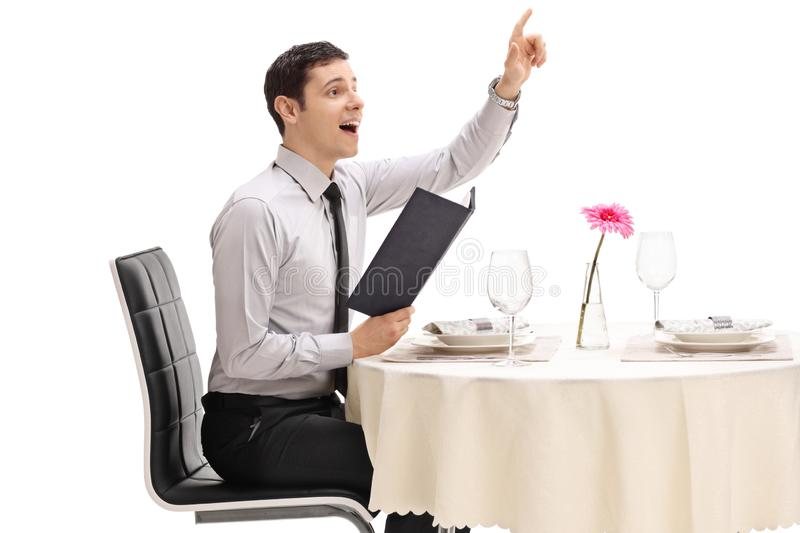 Young man seated at a restaurant table calling the waiter stock image