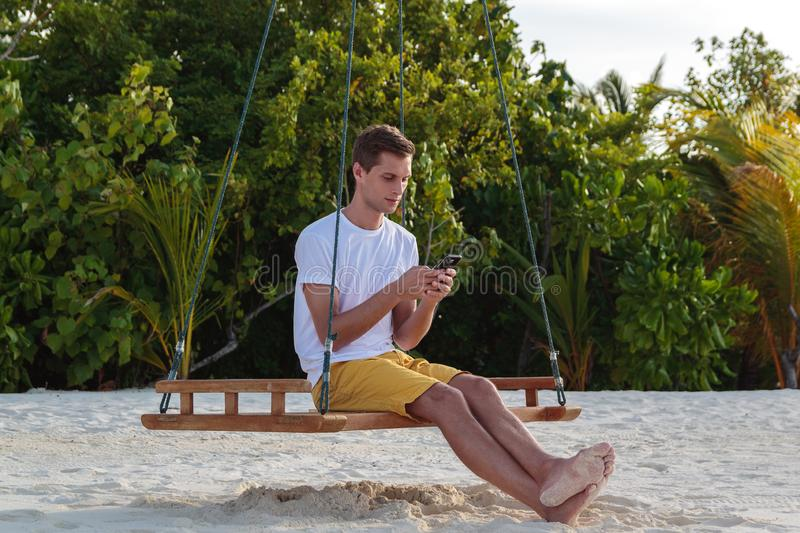 Young man seated on a swing and using his phone. White sand and jungle as background. Male holding a smartphone in a tropical location. roaming free concept royalty free stock image