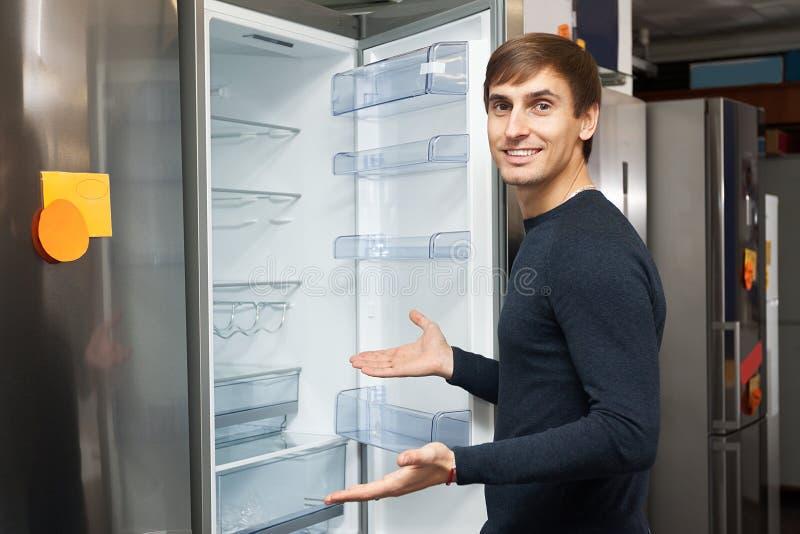 Young man selecting domestic refrigerator. Happy young man selecting domestic refrigerator in supermarket stock image