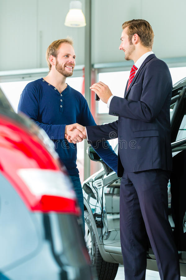 Young man and seller with auto in car dealership. Seller or car salesman and customer in auto dealership, they shaking hands, hands over the car keys and seal stock photo