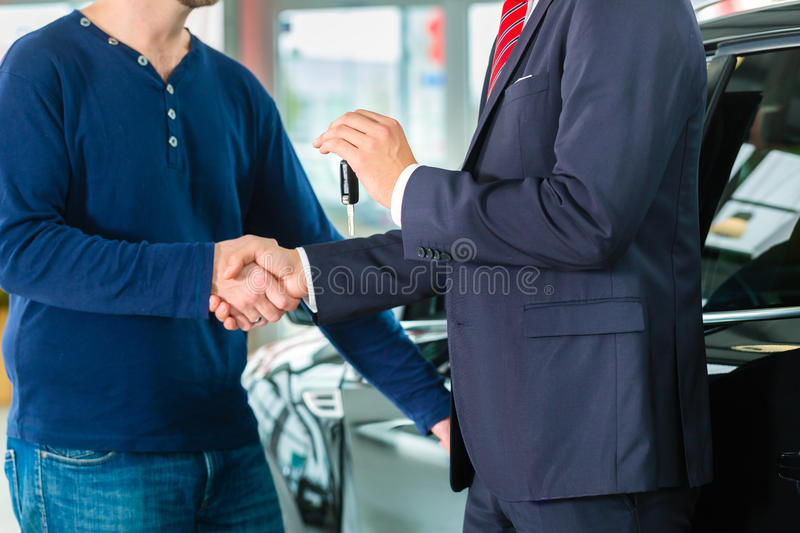 Young man and seller with auto in car dealership. Seller or car salesman and customer in auto dealership, they shaking hands, hands over the car keys and seal royalty free stock images