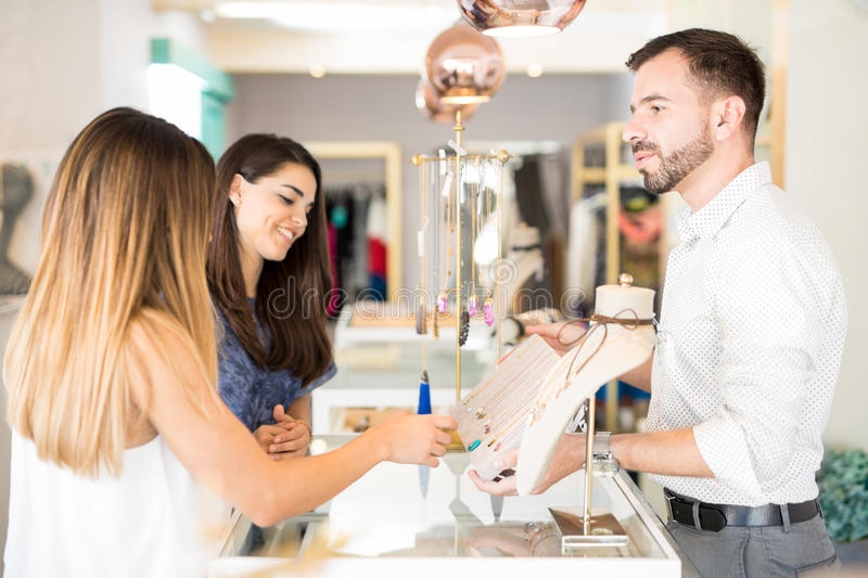 Young man selling jewelry to women stock photo