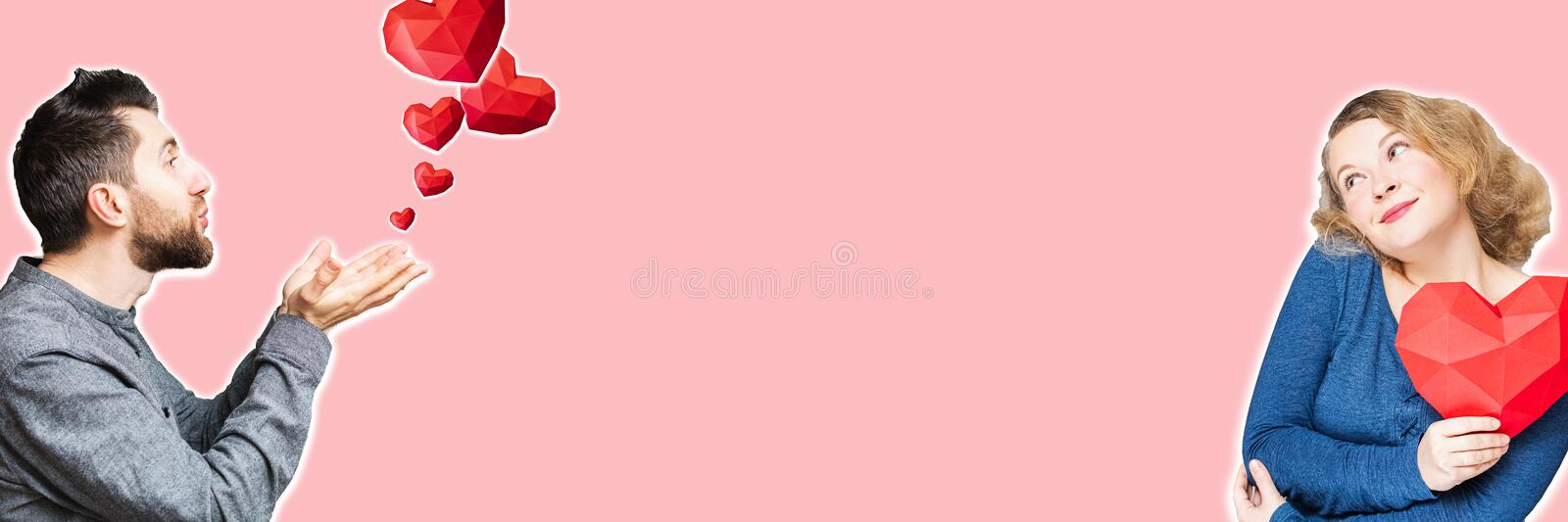 Young man sending air kiss and polygonal diamond shaped red hearts to the woman he loves stock photos