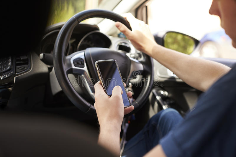 Young Man Sending Text Message Whilst Driving stock images