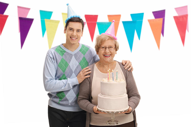 Young man and senior with party hats and birthday cake. Young men and a senior with party hats and a birthday cake isolated on white background stock images