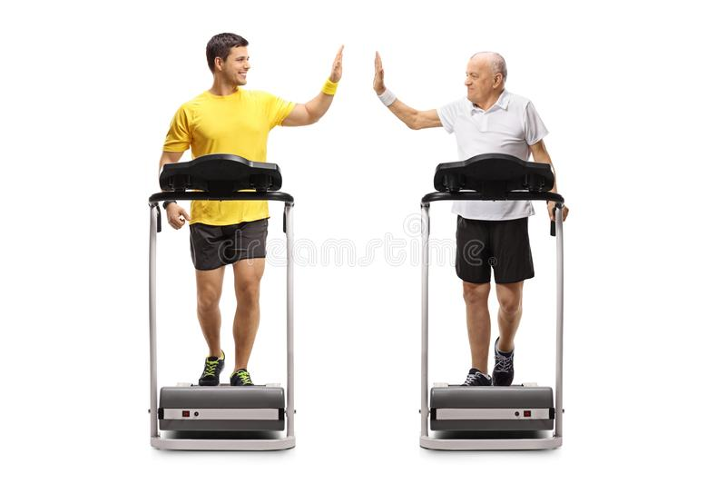 Young man and a senior walking on treadmills and high-fiving each other royalty free stock photos