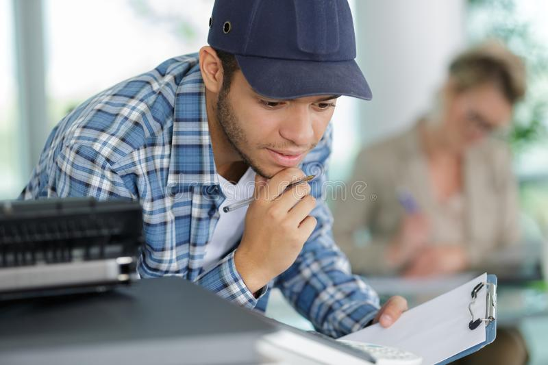 Young man servicing photocopier in office stock photography