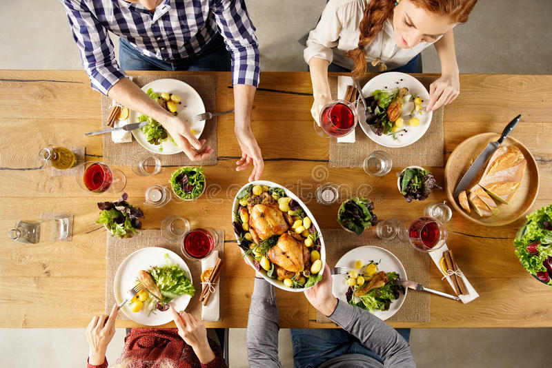 Young man serving food. Top view of men passing food bowl to friend. High angle view of happy young friends eating together at home. Happy men and women having stock photography