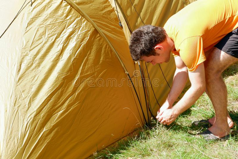Young man set up a tent. Preparation for outdoor recreation. stock photo
