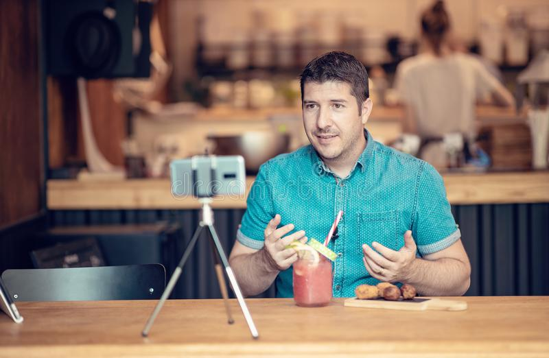 Young man sharing content on streaming platform with smart phone - Vlogging concept on sharing business info on social media stock photos