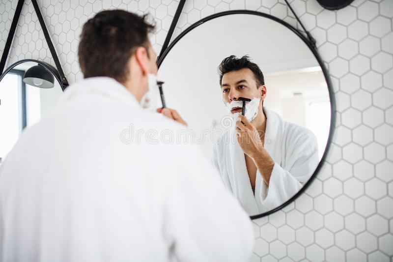 Young man shaving in the bathroom in the morning, daily routine. A young man shaving in the bathroom in the morning, a daily routine royalty free stock photography