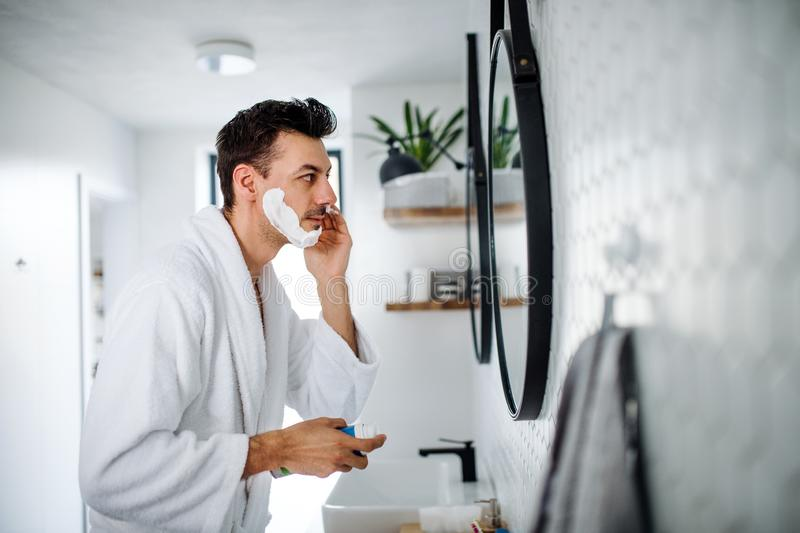 Young man shaving in the bathroom in the morning, daily routine. A young man shaving in the bathroom in the morning, a daily routine stock images