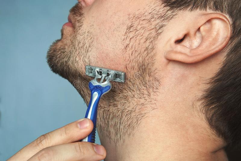 Young man without shaving cream on his face, grooming his beard with straight razor, royalty free stock photos