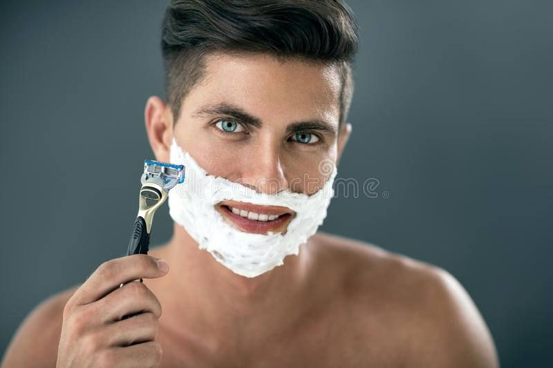 Young man shaving his beard with razor stock images
