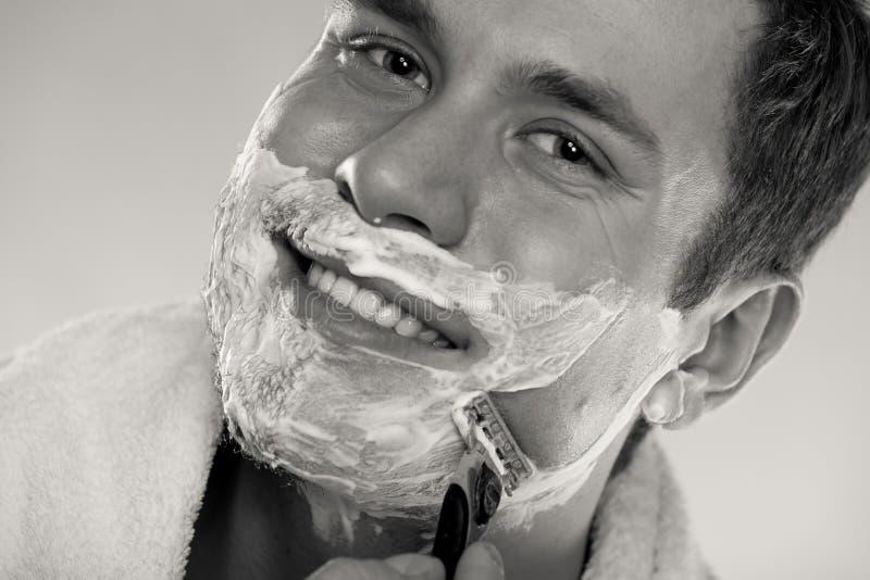 Young man shaving using razor with cream foam. stock photography