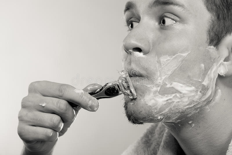 Young man shaving using razor with cream foam. Handsome guy removing face beard hair. Skin care and hygiene. Black and white bw photo royalty free stock photo