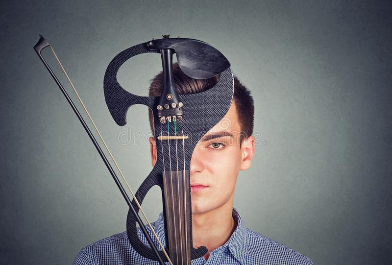 Young man with modern violin instrument. Young man in shirt covering face with violin in modern design looking at camera on gray background stock images