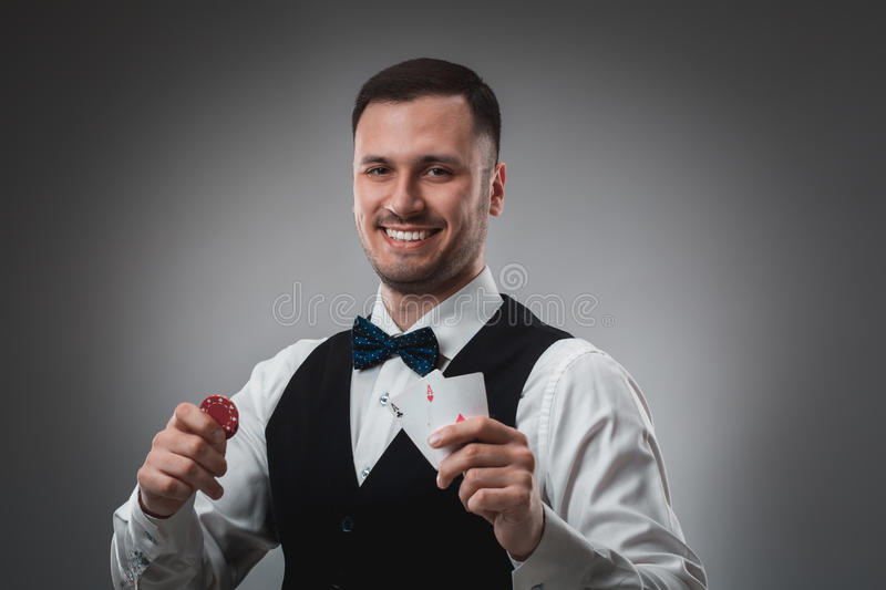 Young man in shirt and waistcoat shows his cards and holds poker chips in his hands, studio shot stock photos
