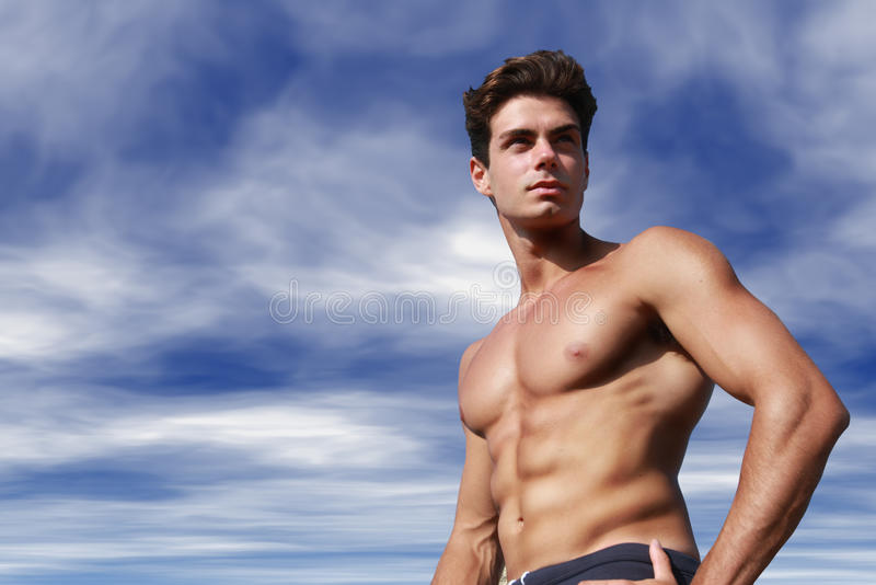 Young man shirtless. Fashion hair style. Sky behind. A young man with a beautiful body and hair style is shirtless with the sky cloudy behind. With one hand on stock photos