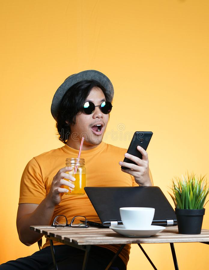 Young Man Shocked and Excited Holding Smartphone While Working o. N Summer Vacation Season Against Yellow Background stock photos