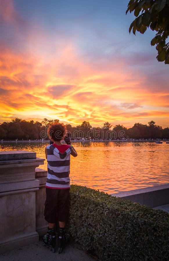 Young man shooting the sunset in Buen Retiro park royalty free stock photo
