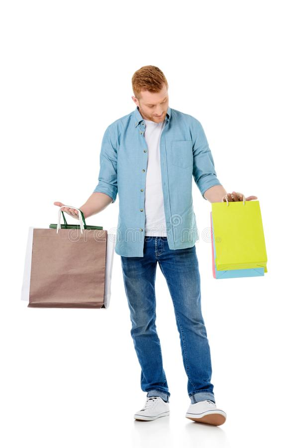 Handsome young man holding colorful shopping bags. Isolated on white royalty free stock photos