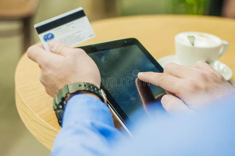 A young man shopping online with a credit card via a tablet computer. A young man shopping online with a credit card via a tablet computer royalty free stock photo