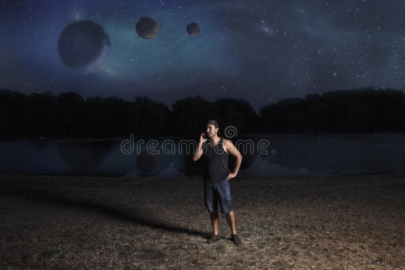 Young man in shorts and cap, at night talking on a mobile phone on the shore of a reservoir against the background of an abstract stock photography