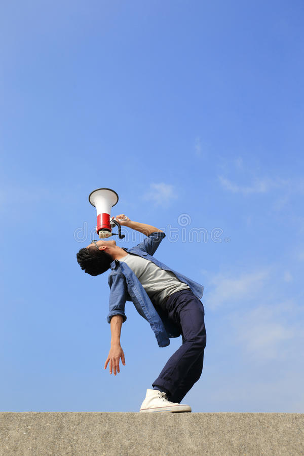 Young man shout megaphone. Young man shout by megaphone with blue sky background, asian stock images