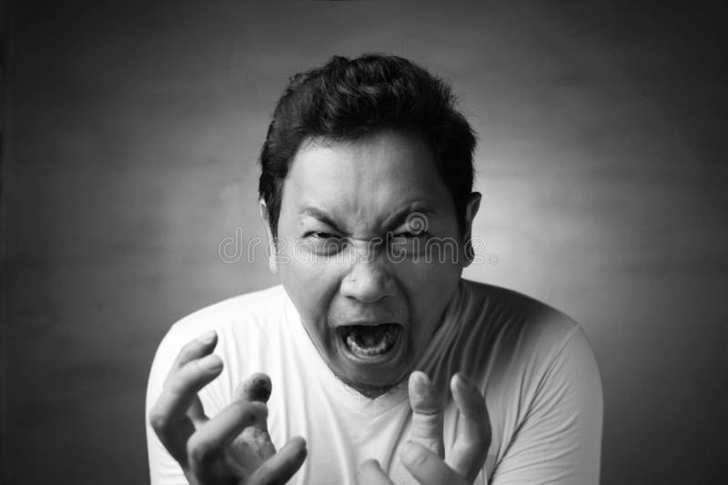 Young Man Shouting, Anger Gesture. Young Asian man wearing white shirt shouting because of anger. Close up head and shoulders, monochrome black white image royalty free stock photos