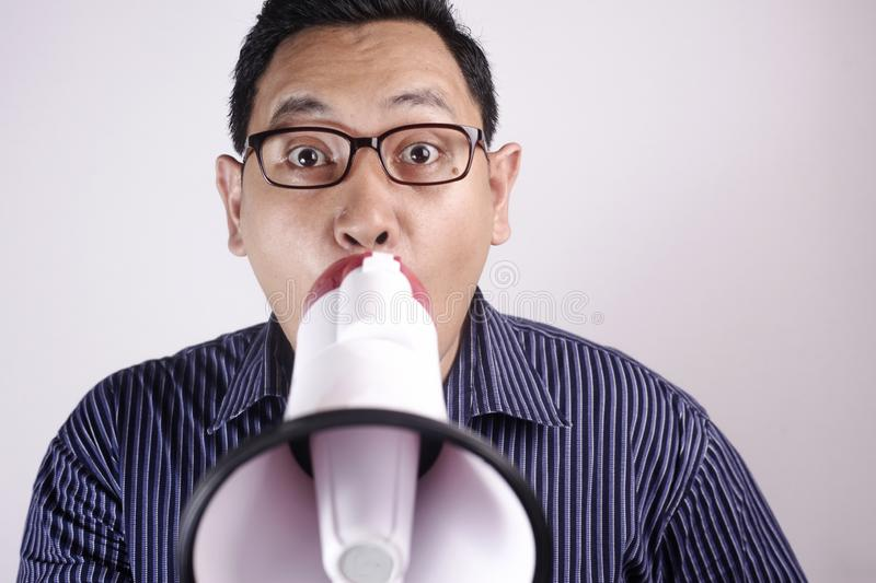 Young Man Shouting with Megaphone, Angry Expression stock photography