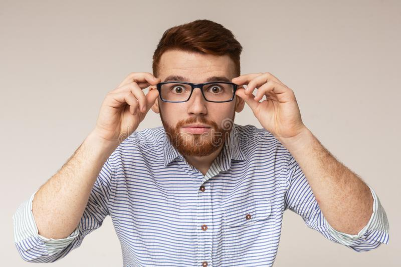 Young man showing his big eyes in glasses royalty free stock photo